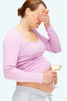 Young pregnant woman avoiding the temptation of alcohol over white background