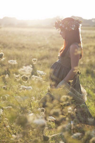 jolie jeune femme enceinte robe verte et couronne de fleurs