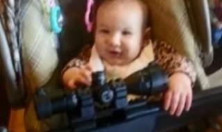 Un bébé pris en photo avec l'arme de son père. Pardon ?